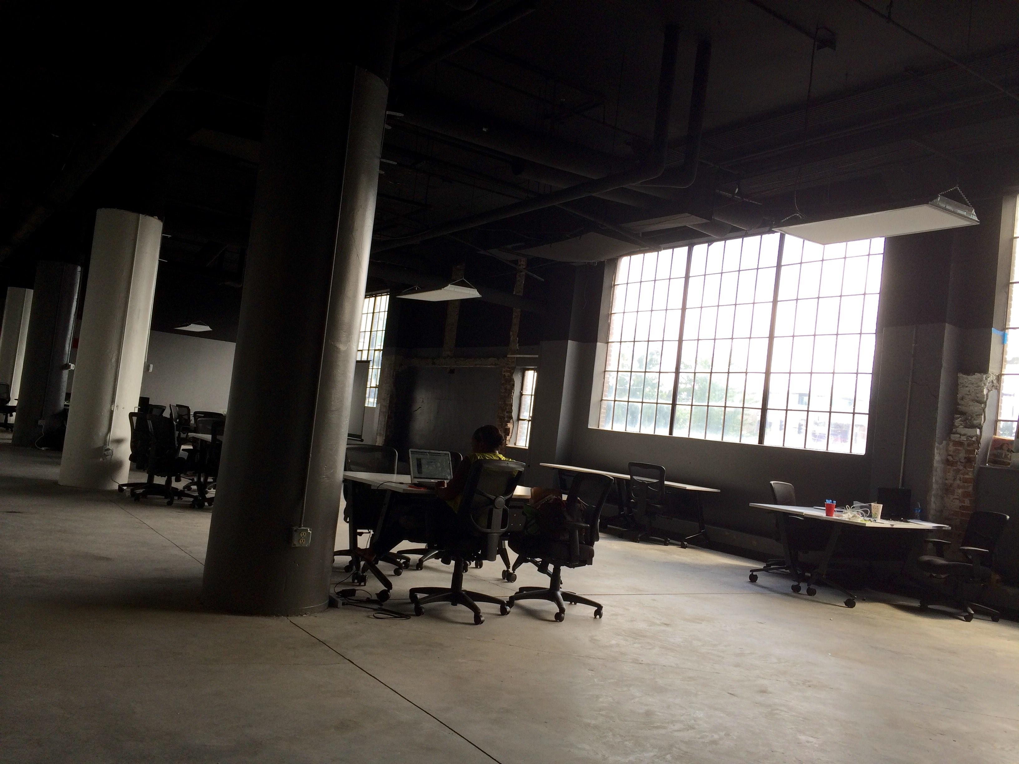 Frau die in einer leeren Halle auf einem Stuhl vor einer Tischgruppe sitzt