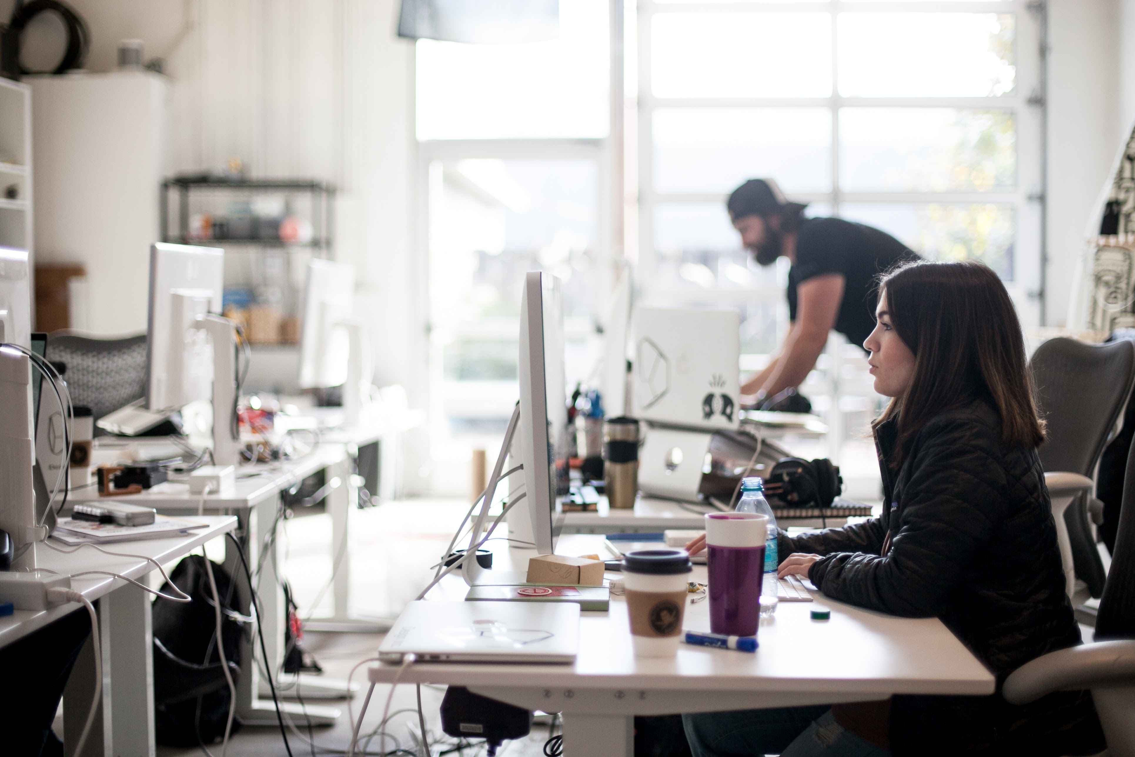 Frau am hell erleuchteten Arbeitsplatz mit Mann im Hintergrund